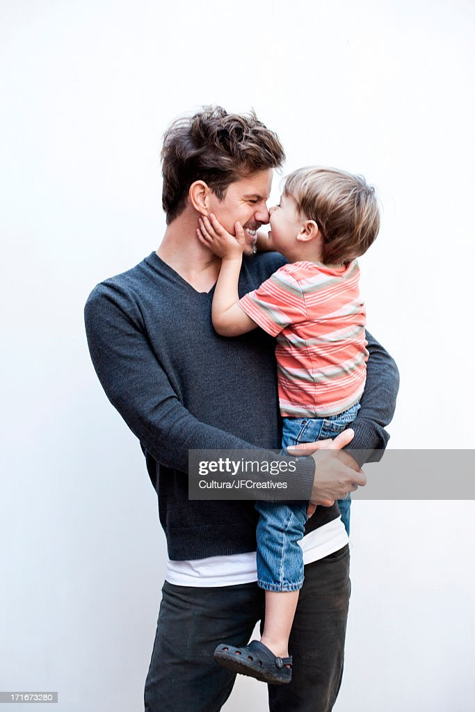 Father holding son, face to face