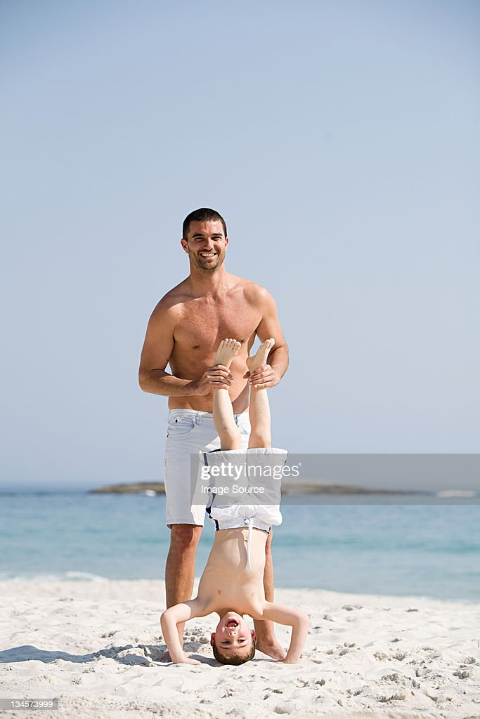 Father holding son in a headstand position on a beach : Stock Photo