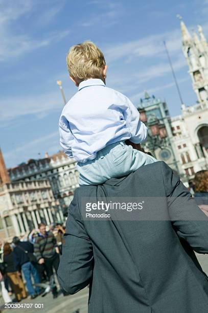 Father holding son (4-5)on shoulders at St. Mark's Square in Venice, Italy, rear view