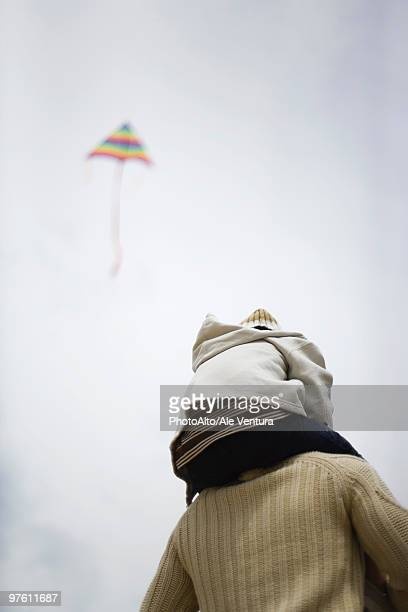Father holding son on shoulders, kite flying in sky in background