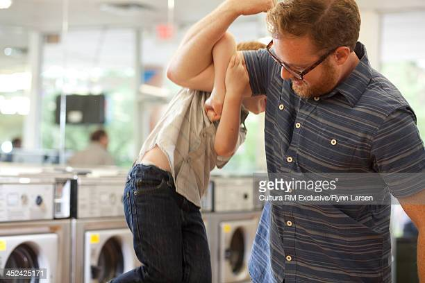 Father holding son up with arm
