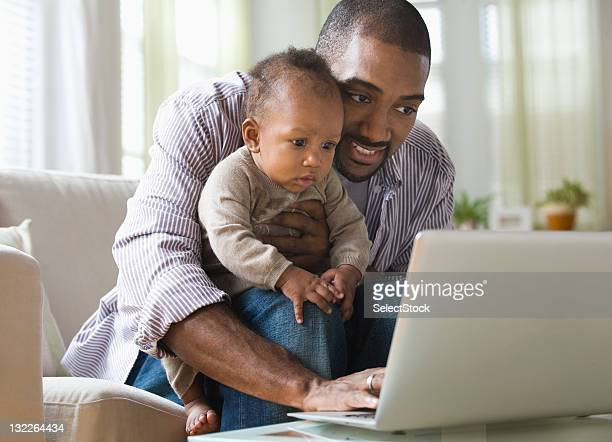Father holding son with laptop