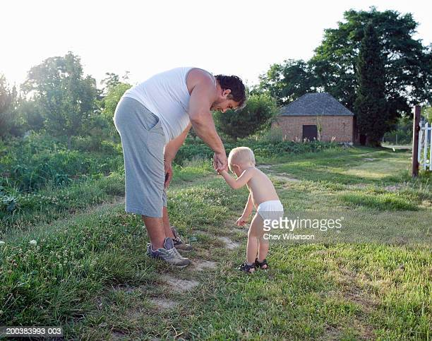 Father holding son's (2-4) hand outdoors, side view
