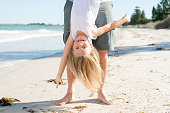 father holding sweet young and lovely blond small daughter by her feet playing having fun on the beach in dad and little girl love concept enjoying Summer holidays