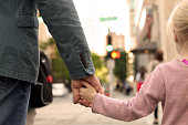 father holding  the daughter/ child  hand  behind  the traffic lights