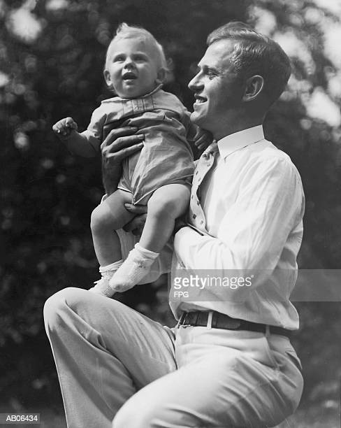 Father holding toddler boy (15-18 months) outdoors (B&W)