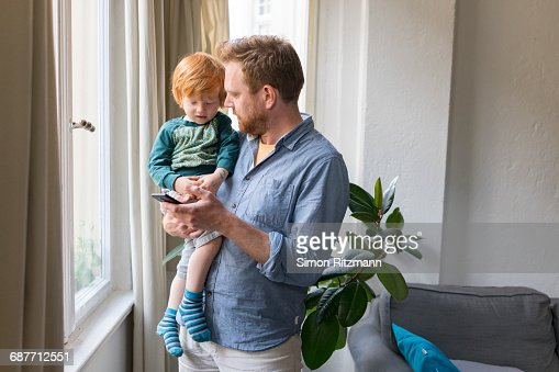 Father holding toddler son using mobile phone