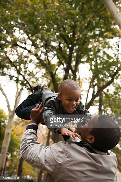 Father holding up toddler son in park