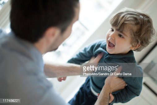 Father holding up toddler son : Stock Photo