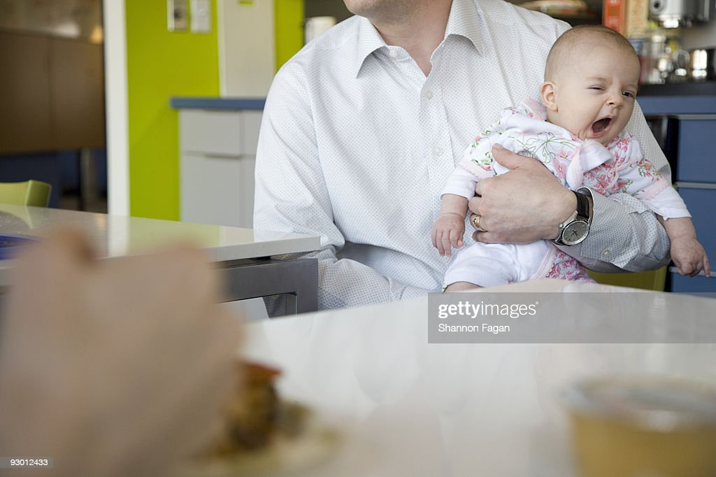 Father holding yawning baby in cafeteria : Stock Photo