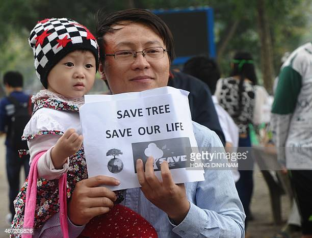 A father holds a placard as he and his young daughter join a rally against a treefelling plan by the municipal authorities in Hanoi on March 22 2015...
