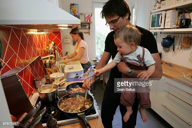 Kostas Kosmas holds his son Leander 16 months while preparing dinner with his wife Annette Wassermann at home after work May 9 2006 in Berlin Germany...