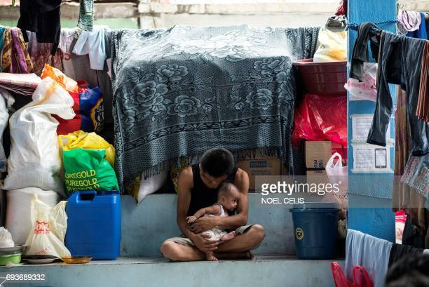 A father holds his baby inside a covered basketball court turned into an evacuation center for the Marawi City evacuees at Maria Cristina Barangay...
