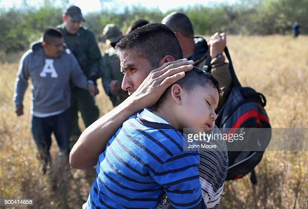 A father holds his sleeping son after they and other undocumented immmigrants were detained by Border Patrol agents on December 7 2015 near Rio...