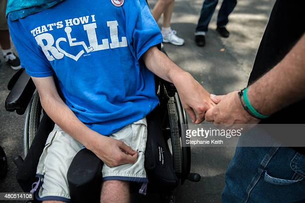A father holds his son's hand during the first annual Disability Pride Parade on July 12 2015 in New York City The parade calls attention to the...