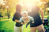 Happy father holds newborn baby on arm while kissing the mother of child. happy family in park, newborn kid and happiness