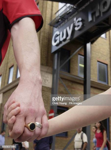 A father holds tightly onto his daughters hand outside Guy's Hospital in London after a woman attempted to abduct a newborn baby from a hospital...