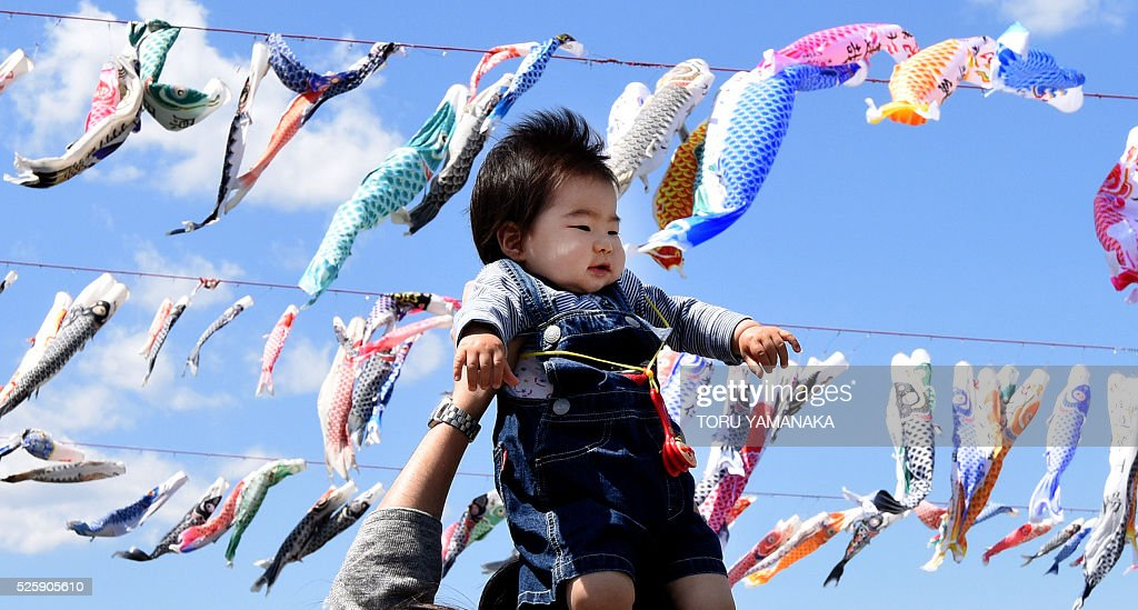 A father holds up his baby under carp streamers fluttering in a riverside park in Sagamihara, suburban Tokyo, on April 29, 2016 ahead of May 5 Children's Day in Japan. Some 1,200 carp streamers were hoisted over the Sagami River to celebrate the annual holiday of Children's Day - part of Japan's 'Golden Week' holiday which is traditionally one of the busiest travel times of the year. / AFP / TORU