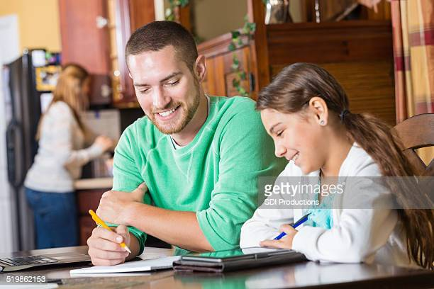 Father homeschooling young daughter in family kitchen