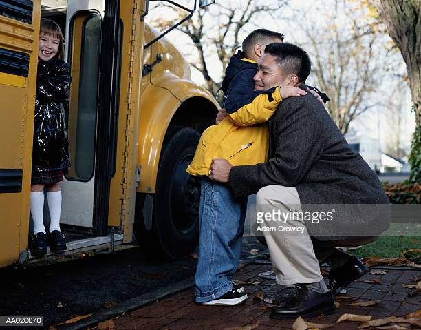 Father Hugging His Son as He Boards a School Bus