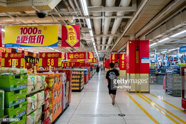 A father hugging his son walks in a Walmart supermarket According to the financial report of the first quarter in 2017 total sales of WALMART in...