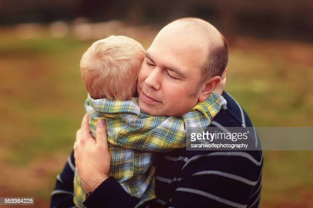 father hugging his two year old son