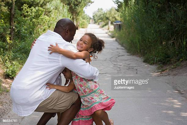 Father hugging little girls