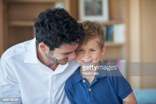 Father hugging son in living room : Stock Photo