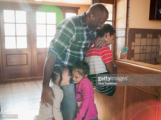 Father hugging teen son and twin daughters