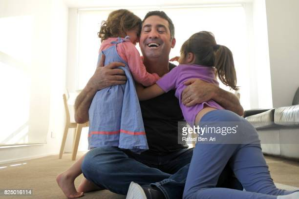 Father hugs his daughters at home
