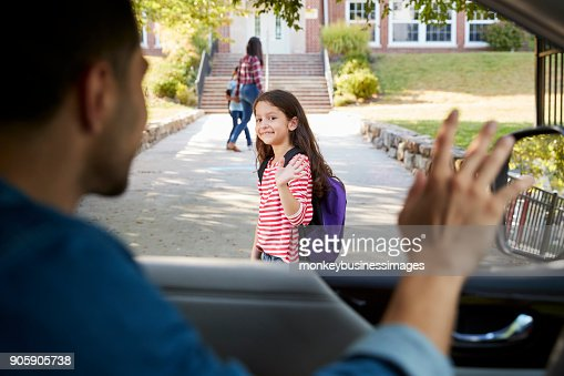 Father In Car Dropping Off Daughter In Front Of School Gates : Stock Photo
