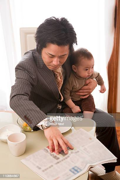 Father in Full Suit Holding Baby Girl and Reading Newspaper