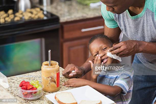 Father in kitchen taking care of little boy, wiping nose