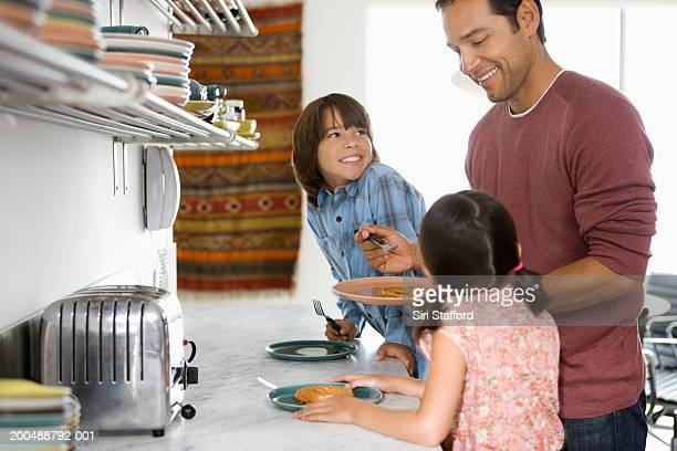 Father in kitchen with children (6-10)