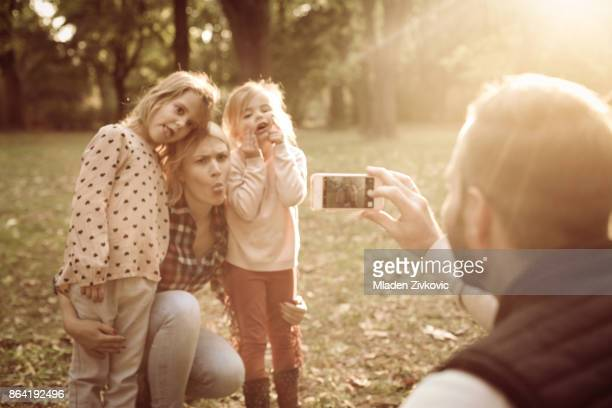 Father in park taking self portrait of his family.
