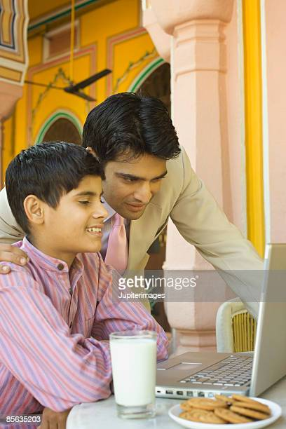Father in son in front of laptop computer with glass of milk and cookies, India