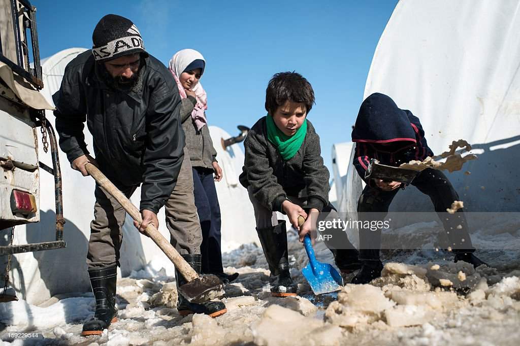 A father is helped by his boys to remove snow in front of their tent in a Syrian refugees camp in Azaz, near the Turkish border, on January 10, 2013 after snow falls. Snow carpeted Syria's war-torn cities but sparked no let-up in the fighting, instead heaping fresh misery on a civilian population already enduring a chronic shortage of heating fuel and daily power cuts. AFP PHOTO / EDOUARD ELIAS