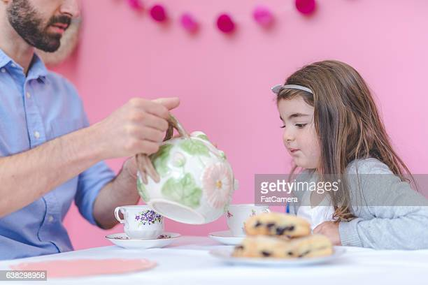 A father is pouring tea for his young daughter while