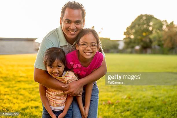 Ein Vater steht mit seiner Töchter und gibt