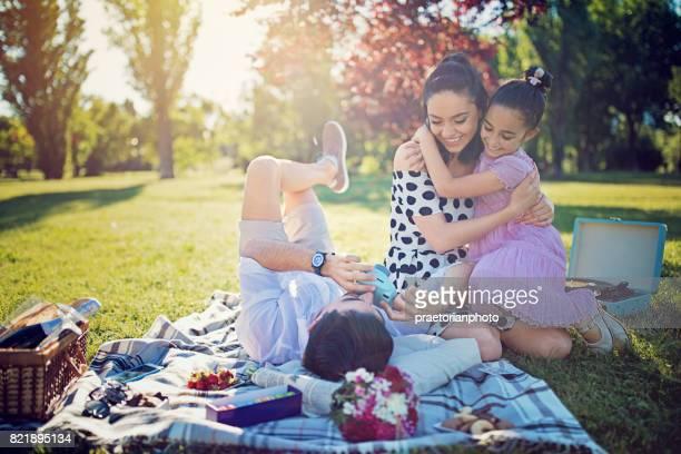 Père fait des photos de sa tendre épouse et sa fille à pique-nique dans le parc