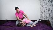 Family is having fun. Girl is laying down on sofa. Her brother lies on top of her. The boy is tickling the girl and father is tickling them both.
