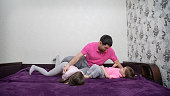 Family is having fun. Girl is protecting oneself from father's hands. She is laughing. Boy is looking at father and talking something. Main colors are white, pink, purple, gray and black.