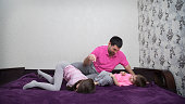 Family is having fun. Girl is lying belly down and laughing. Boy is looking at father and talking something. Main colors are white, pink, purple, gray and black.