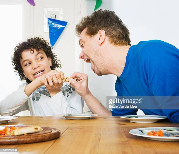 Father is trying to steal food of son's plate.