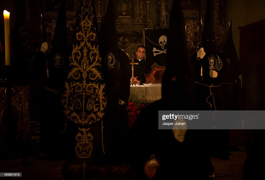 Father Jesus Criado Caballero stands on the altar amid penitents of the Cofradia del Santisimo Cristo del Silencio y la Expiracion brotherhood inside their church at the end of a holy week procession on March 29, 2013 in Luque near Cordoba, Spain. The origin of this small brotherhood, which uses a skull with crossed shins prominently as their symbol, referring to the mortality and short duration of life but also to the triumph of Jesus over death, dates back to the fifties when a group of young catholic's came up with the idea of forming the brotherhood. Since its founding the brotherhood has a strict penitential character with one of its aims being the public prayer of the Stations of the Cross in the early hours of Good Friday through the streets of this small Andalusian town. Home to the brotherhood is the San Nicolas de Tolentino convent church which was founded in 1626 and dedicated to Our Lady of Grace.