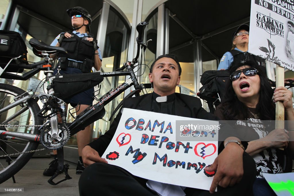 Father Jose Landaverde and Emma Lazano sit in front of the building which houses immigration court during a protest May 15, 2012 in Chicago, Illinois. The two where later arrested along with at least two others at the protest where demonstrators were calling for immigration reform. This was the second day of protests in what is expected to be a full week of demonstrations as the city prepares to host the NATO Summit May 20-21.