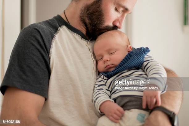father kisses sleepy newborn