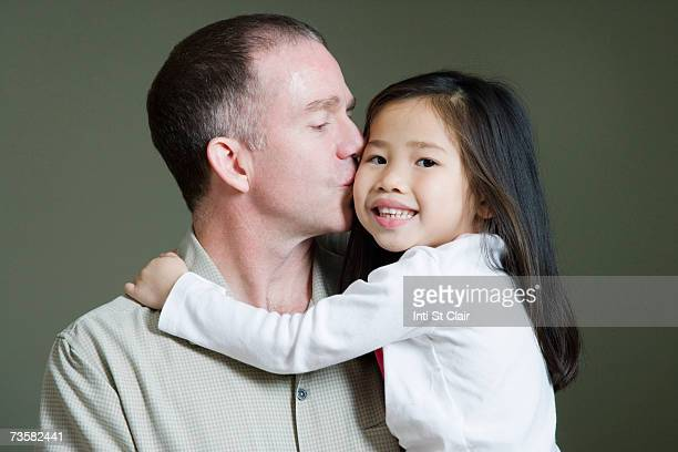 Father kissing adopted Chinese daughter's cheek (3-5)