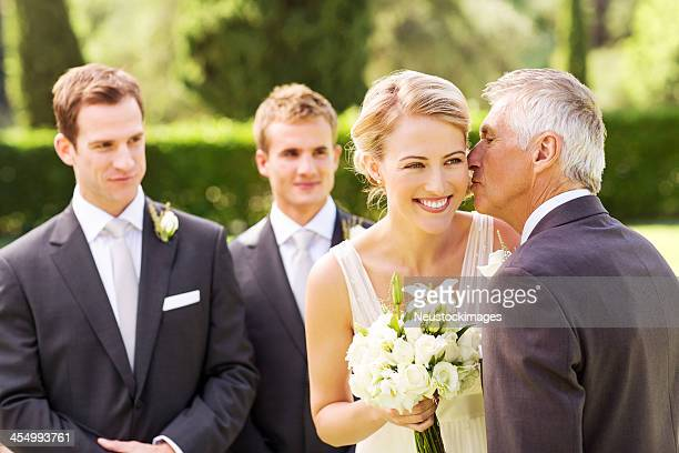 Father Kissing Bride On Cheek During Outdoor Wedding