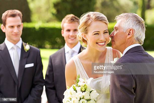 Father Kissing Bride On Cheek During Wedding Ceremony